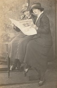 A sepia photograph of two women wearing early twentieth-century suits and hats, sitting outside on a wooden table reading a newspaper titled 'Suffragette'