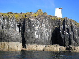 Colour photograph of black cliffs. The top of a white lighthouse is visible behind the cliffs.