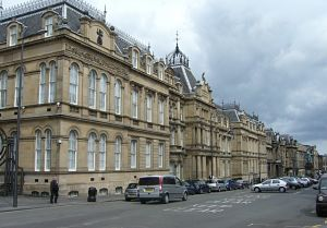 A colour photograph of a large old victorian building with a car park in front of it. The stone of the building is a light brownish yellow colour. It has two floors, both of which are covered in several large arched windows, and there is a central doorway with pillars and a domed cupola on the top.