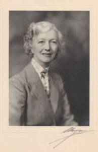 A black and white portrait photograph of a woman, in a cream-coloured cardboard mount. The woman has short, light, curly hair and is wearing a grey suit.