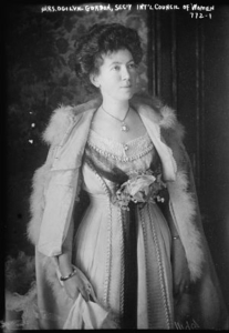 A black and white photograph from the nineteenth or early twentieth century of a woman wearing an ornate beaded dress and fur cape. She is standing up trimuphantly and looking slightly away from the camera, to the right. She has dark hair pinned up above her head and is wearing a necklace with a large, embellished white pendant. She also has a dark tulle sash or stole draped over the dress, which comes together in the middle with a bouquet of flowers on her bust. Her right hand is holding the lower half of the cape. In the background there is a dark wooden door and some floral patterned wallpaper. There is a note on the top of the photograph in handwritten text which reads 'Mrs Ogilvie Gordon, Sec'R Int'l Council of Women, 7-2/1'