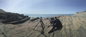 Colour panoramic photograph of a woman sitting on the flat surface of a rocky cliff. She is sitting next to a large tripod-like contraption which is connected to a laptop on top of a box. She is looking away from the camera, towards the laptop. The sky is blue and sunny.