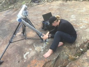 Colour photograph of a woman sitting barefoot on a rocky surface adjusting a tripod-like contraption connected to a laptop. the woman is dressed in black jeans, a black top and a black baseball cap.