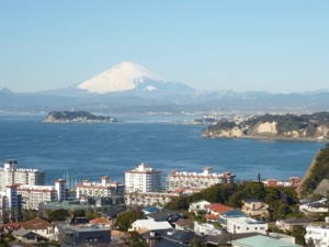 An old colour photograph of a japanese bay with buildings in the foreground and a snow-topped mountain in the background, across blue sea