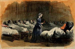 A coloured wood engraving of a nurse wearing a long navy blue dress, a headscarf and holding a red candle, surrounded by patients in small wooden beds with white sheets. The room is very dark and the light is focused on the nurse.