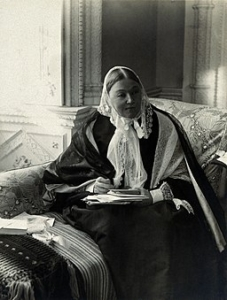 A black and white photograph of florence nightingale in the later stages of her life. She is sitting in what appears to be an ornate room on a patterned chaise longue, wearing long layered robes in balck and white and a white head shawl. She is holding some papers and a pen, and looking away towards the left of the camera.
