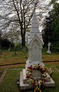 A colour photograph of a turret style gravestone with a red and white floral wreath at its based. There is a tree in the background.