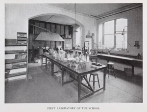 A black and white photograhp of a laboratory room with a central table covered in miscellaneous jars and pots, a bookcase to the left with scientific publications, and a large window and lab bench to the right. Light is streaming in through the window and onto the table.